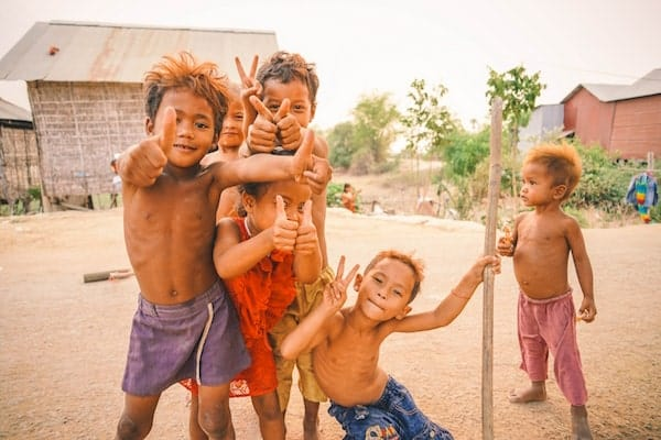 6 poor but happy children making peace signs