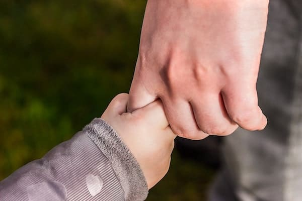 Parent holding toddler's hand