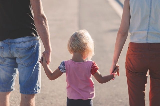 Mom and Dad holding daughter's hands