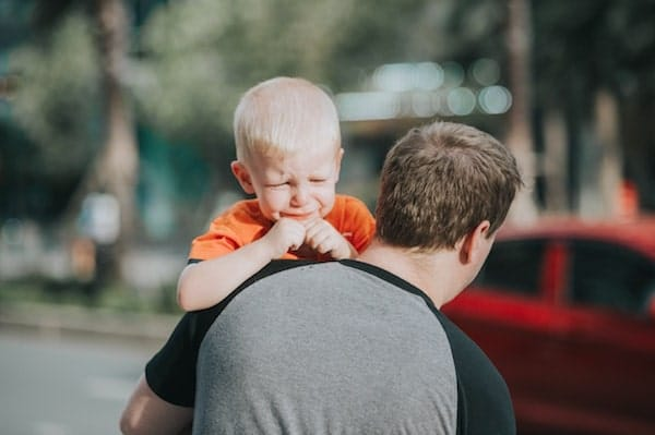 angry and aggressive toddler being carried gently by father