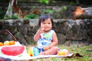 Baby girl sitting on blanket feeding herself picnic foods