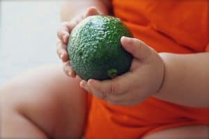 Baby holding a green avocado