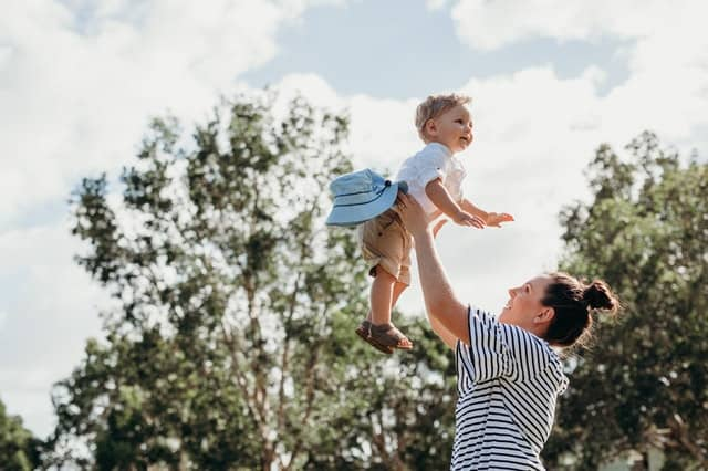 Mother throwing toddler son up in the air