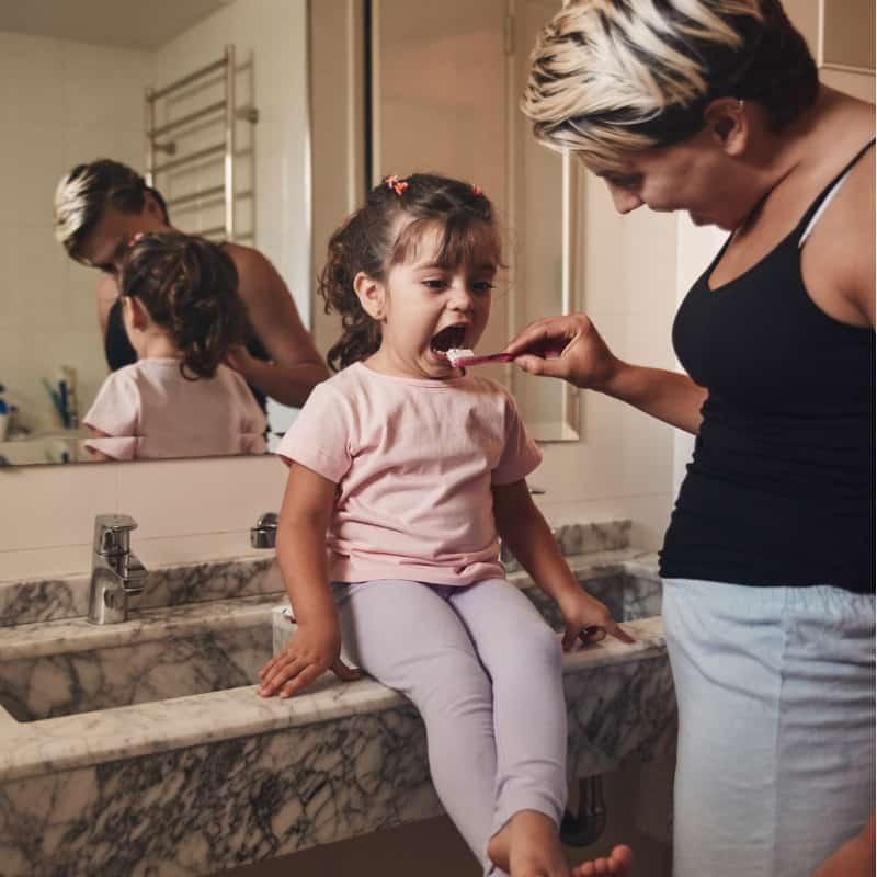 little girl brushing teeth with Mom