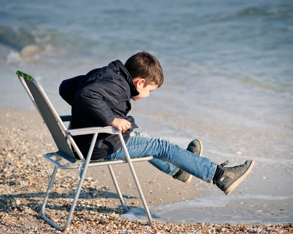 Boy lifting legs on seashore