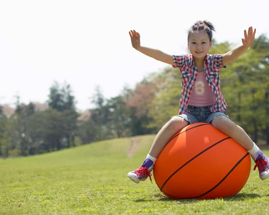 Girl balancing on giant basketball
