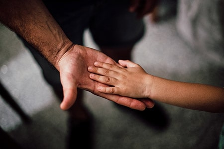 Child playing hand on a dad's hand