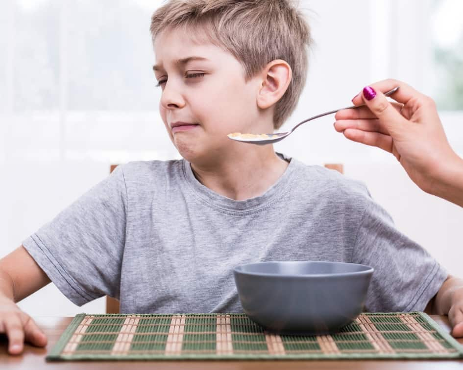 Boy refusing food on a spoon